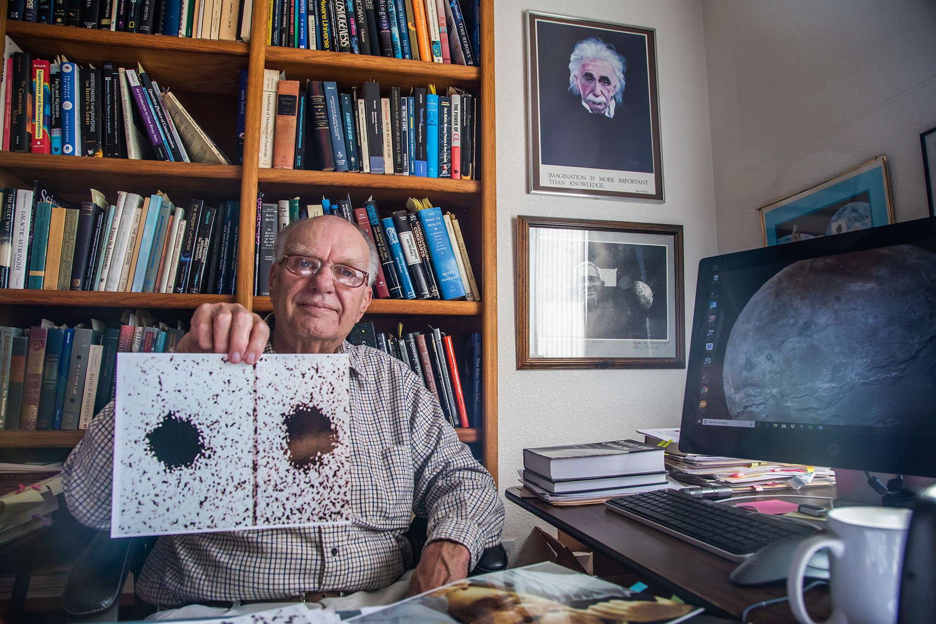 Jim Christy holding his original Charon discovery image in 2018.