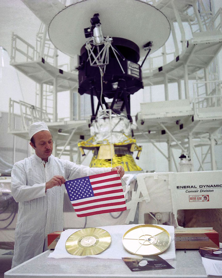 technician holding u.s. flag with voyager spacecraft in background