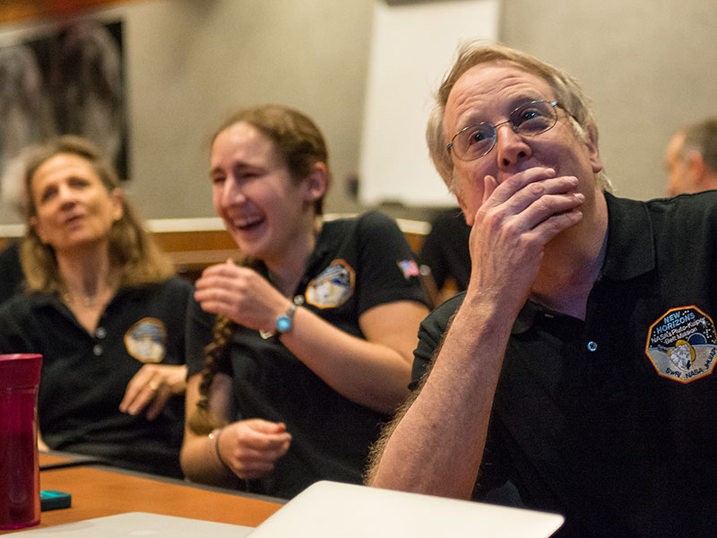 Two women and a man smiling at photos coming down from Pluto in 2015,