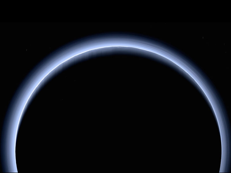 Blue haze encircling dark orb of Pluto.