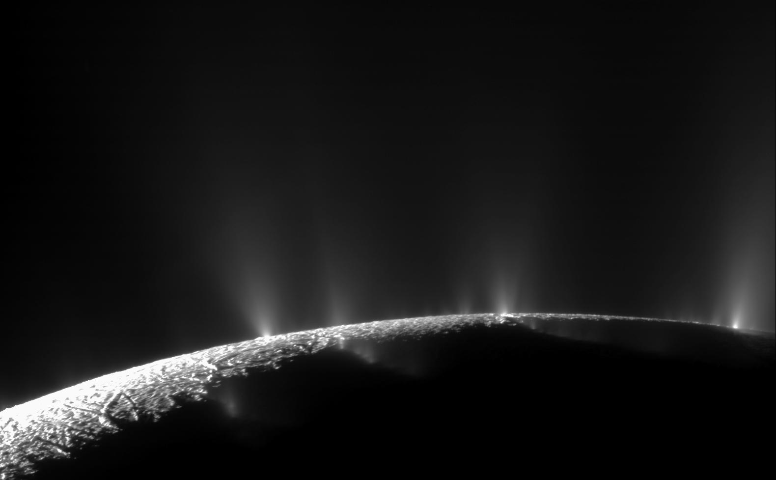 Black and white image of jets of material blasting off Enceladus.