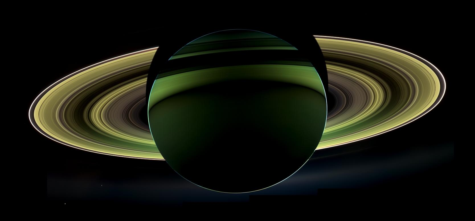 An image of a backlit, green-colored Saturn