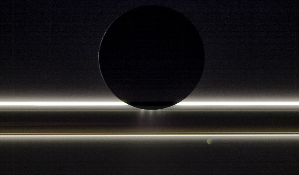 Enceladus and Saturn's rings illuminated by sunlight.