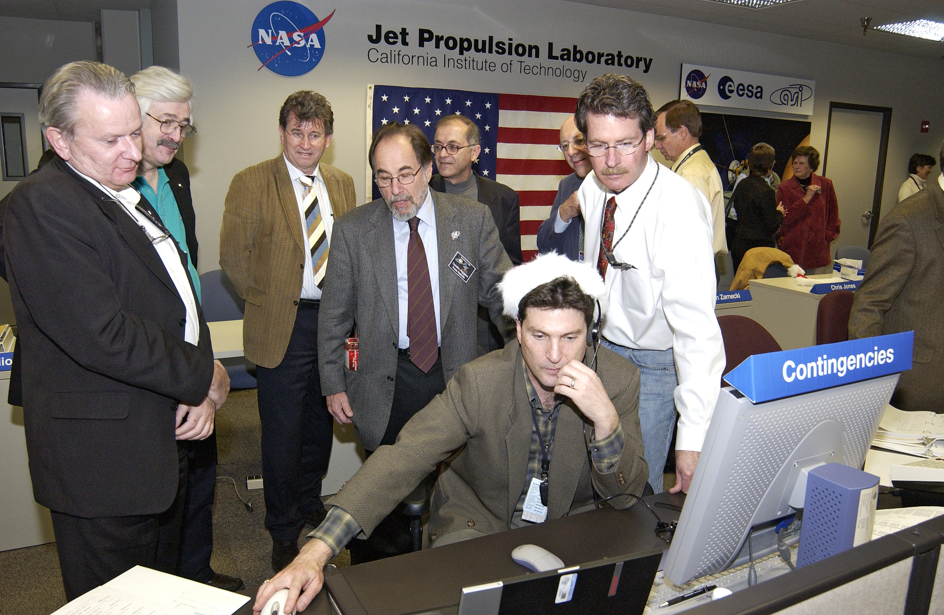 Group of men gathered at console.Credit: NASA/JPL-Caltech