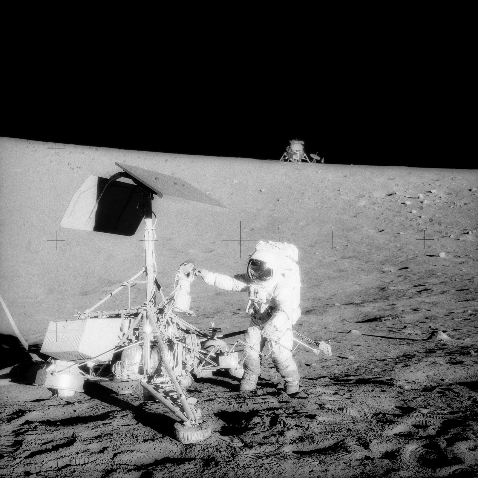 Astronaut standing next to robotic spacecraft on the surface of the Moon.