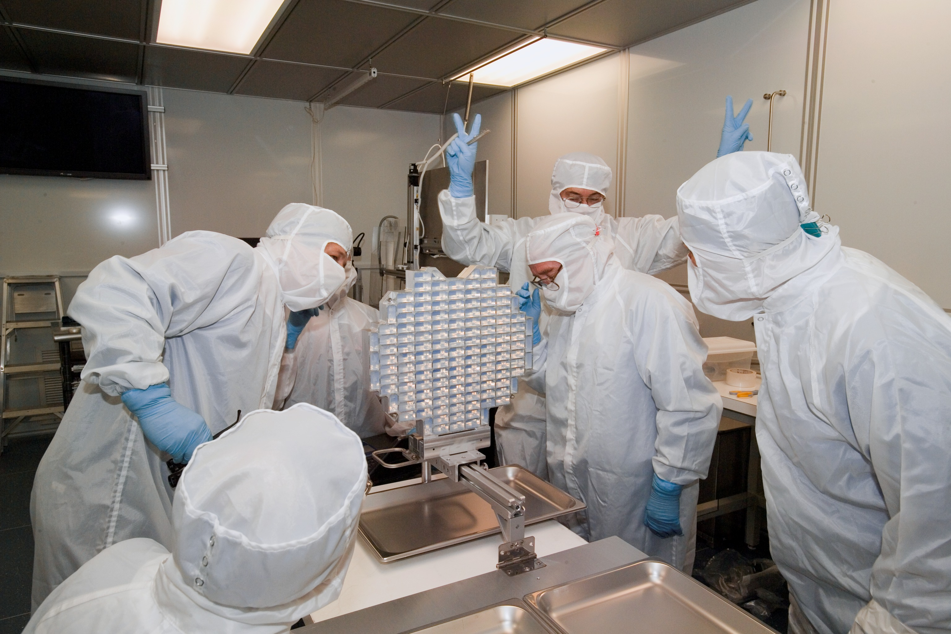 Five people in protective gear looking at Stardust sample collector.