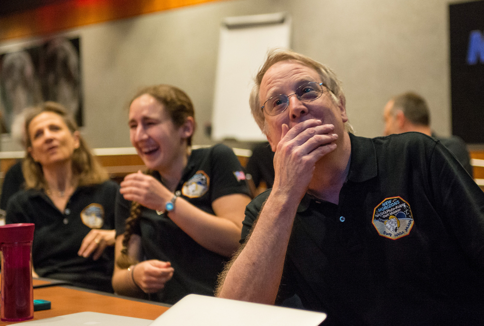 Two women and a man react with joy at seeing the first images of Pluto.