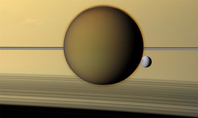 Dione can be seen through the Titan haze in this view of the two posing before the planet and its rings from Cassini.