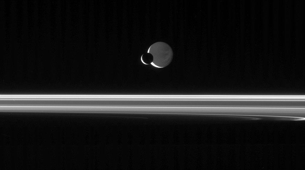 The Cassini spacecraft looks across the unlit ringplane as Mimas glides silently in front of Dione.