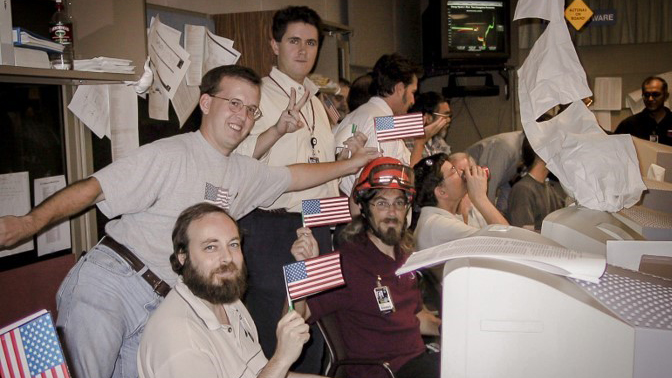 Team waving flags in mission control.