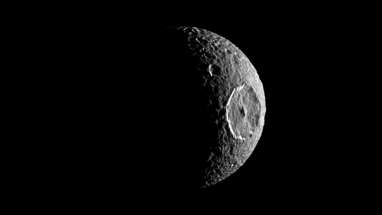 Moon with giant impact crater on its side.