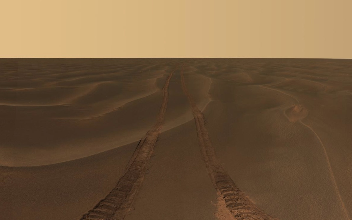 vast plain of dunes with rover tracks leading to horizon