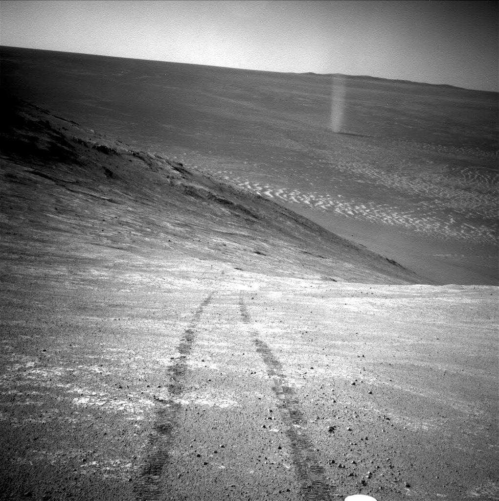 rover tracks on a hillside with a dust devil seen in the distance