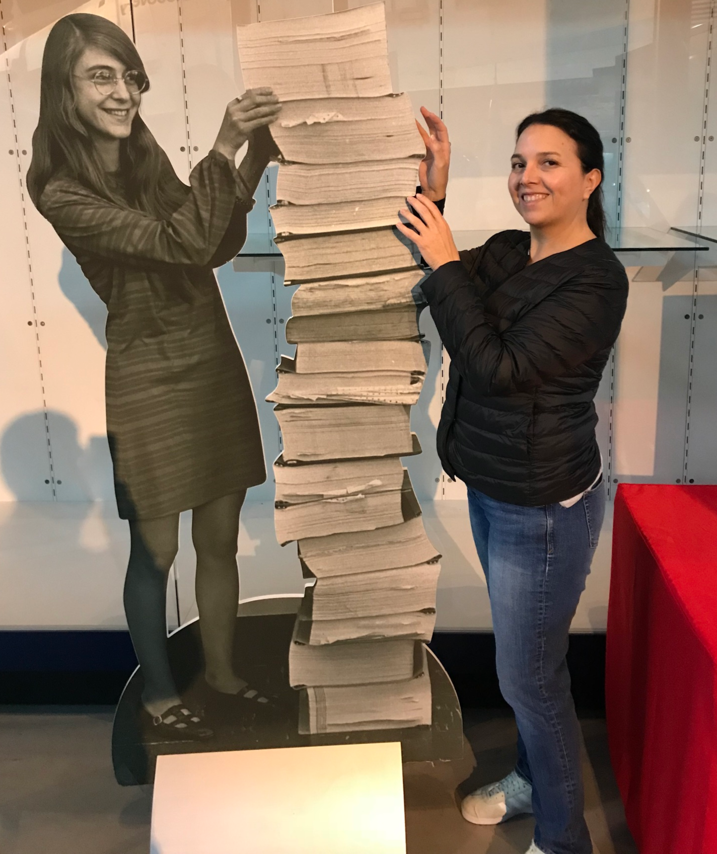 Elisa Quintana poses with a cutout of Margaret Hamilton and the code Hamilton wrote to send NASA astronauts to the Moon.