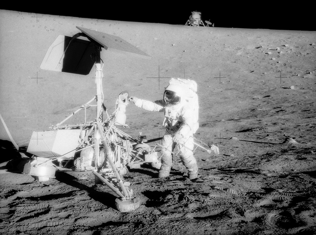 Astronaut and robot together on the Moon.