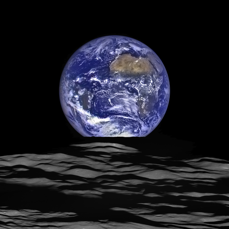 earth rising full over lunar horizon