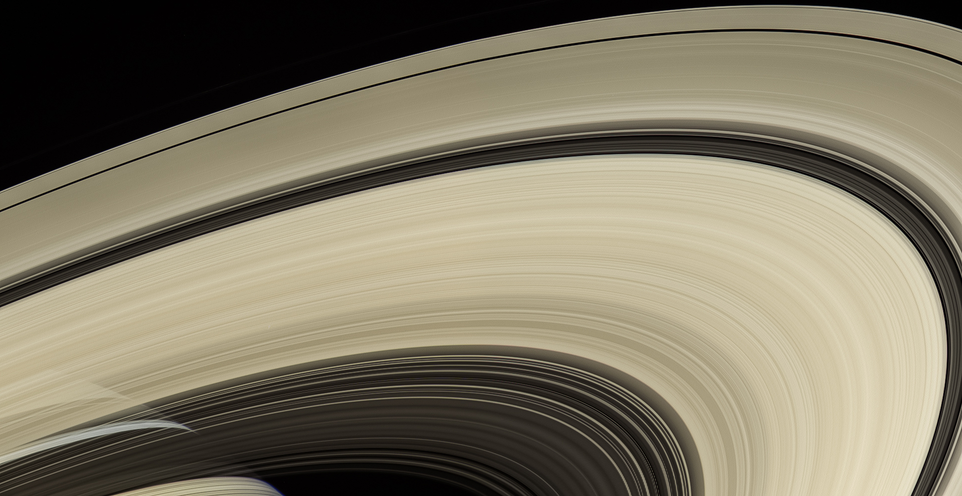 broad arc of rings with saturn visible behind