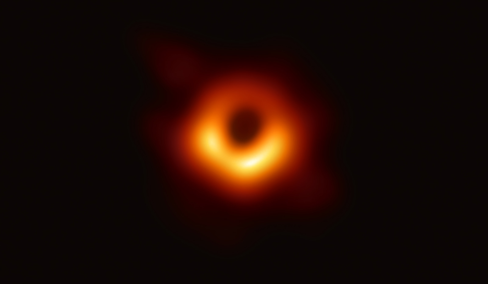 Dark spot of a black hole ringed with bright orange light.