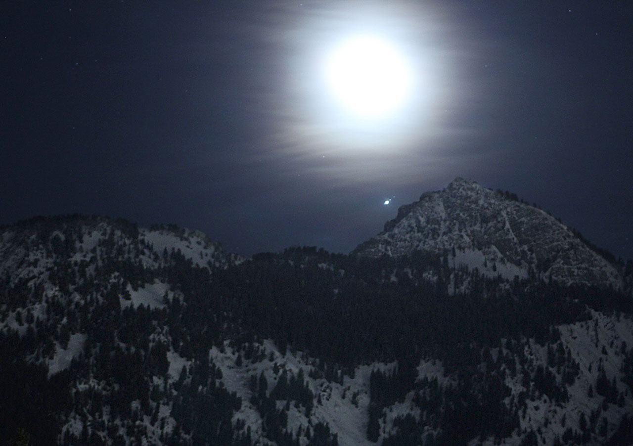 The Moon, Jupiter and its four largest moons above snowy mountain peaks in Utah.