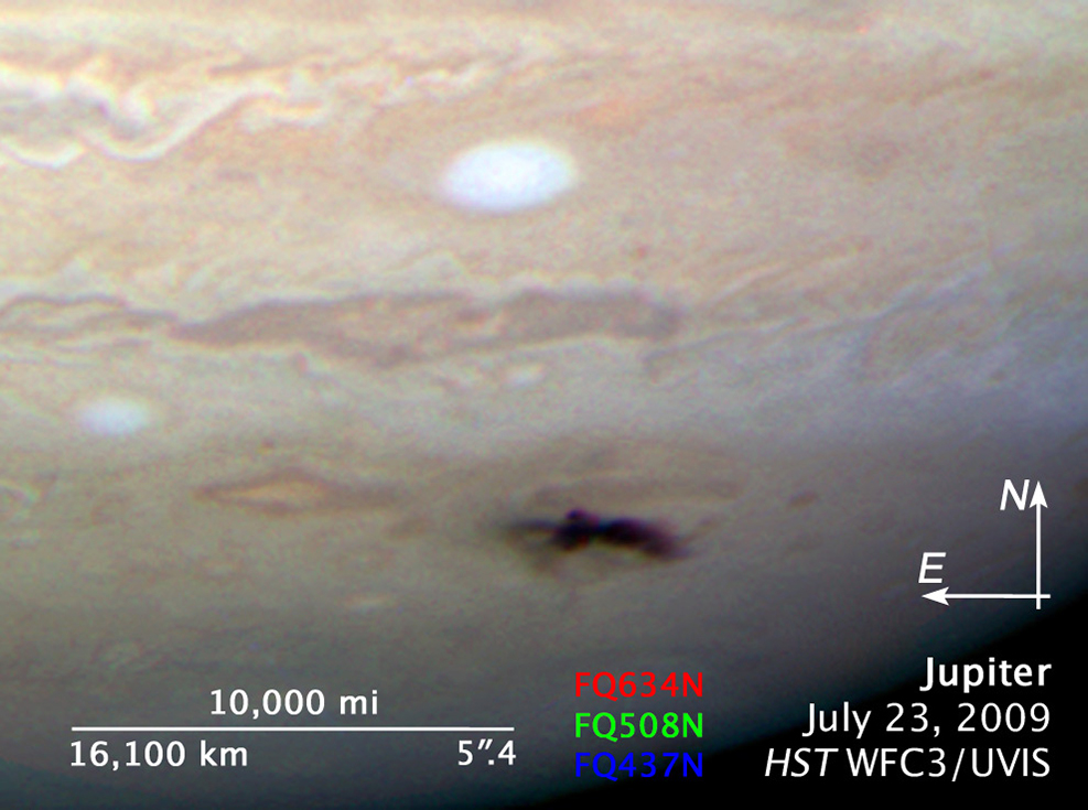 Impact spot on Jupiter with scale showing it is about 6,000 miles long.