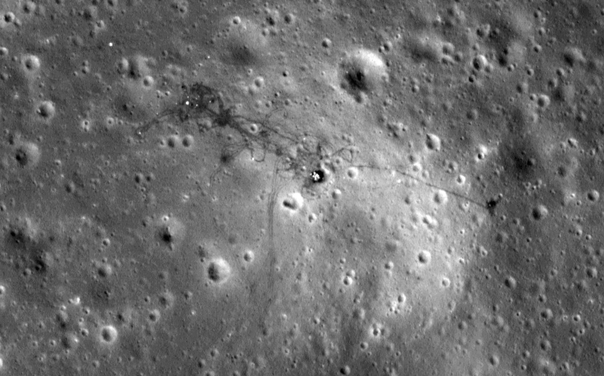 plain viewed from above with craters, spacecraft and foot trails visible