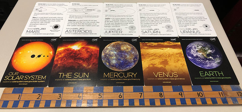 A partial set of trading cards set out along a 12-inch ruler for scale.