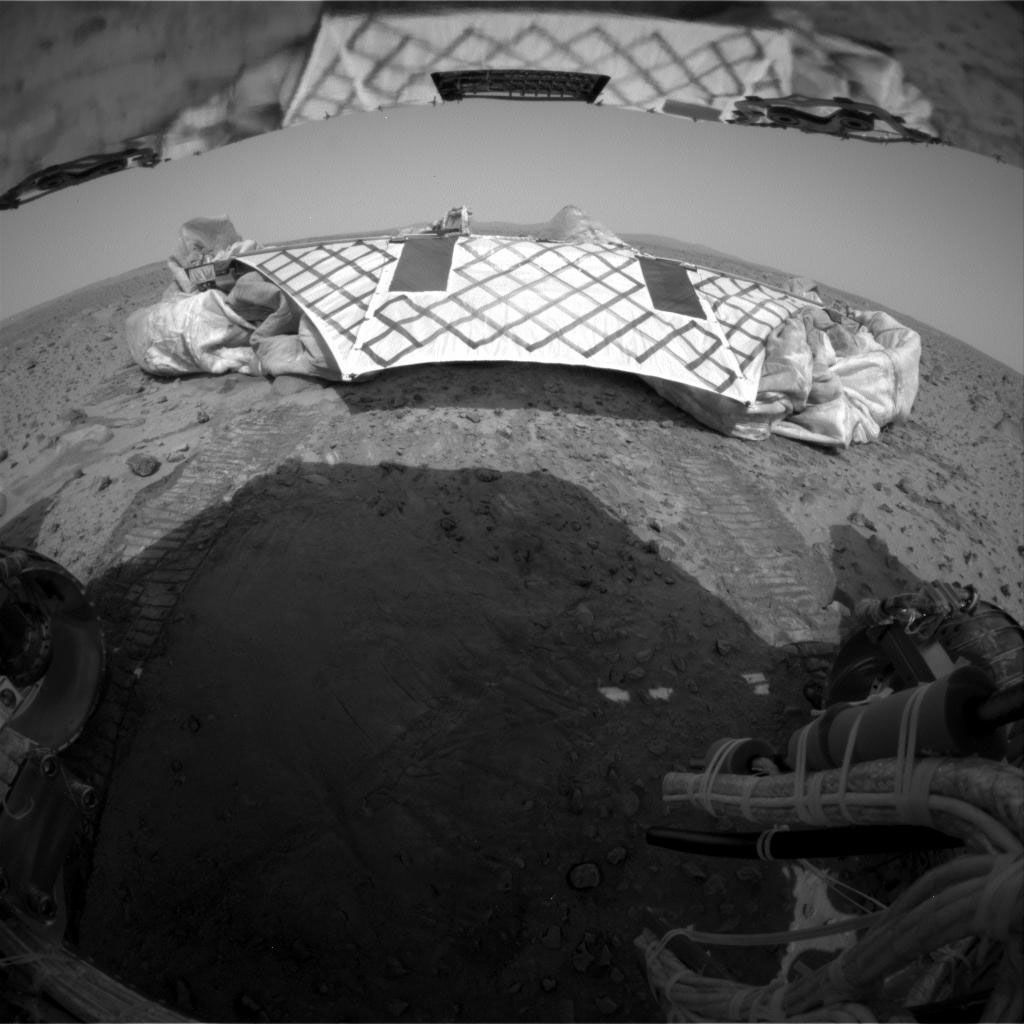 Image of landing platform on Mars with rover wheel tracks in foreground.