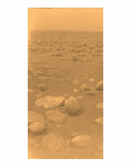 Small pebbles stretch off into the distance of the orangish surface of Titan.