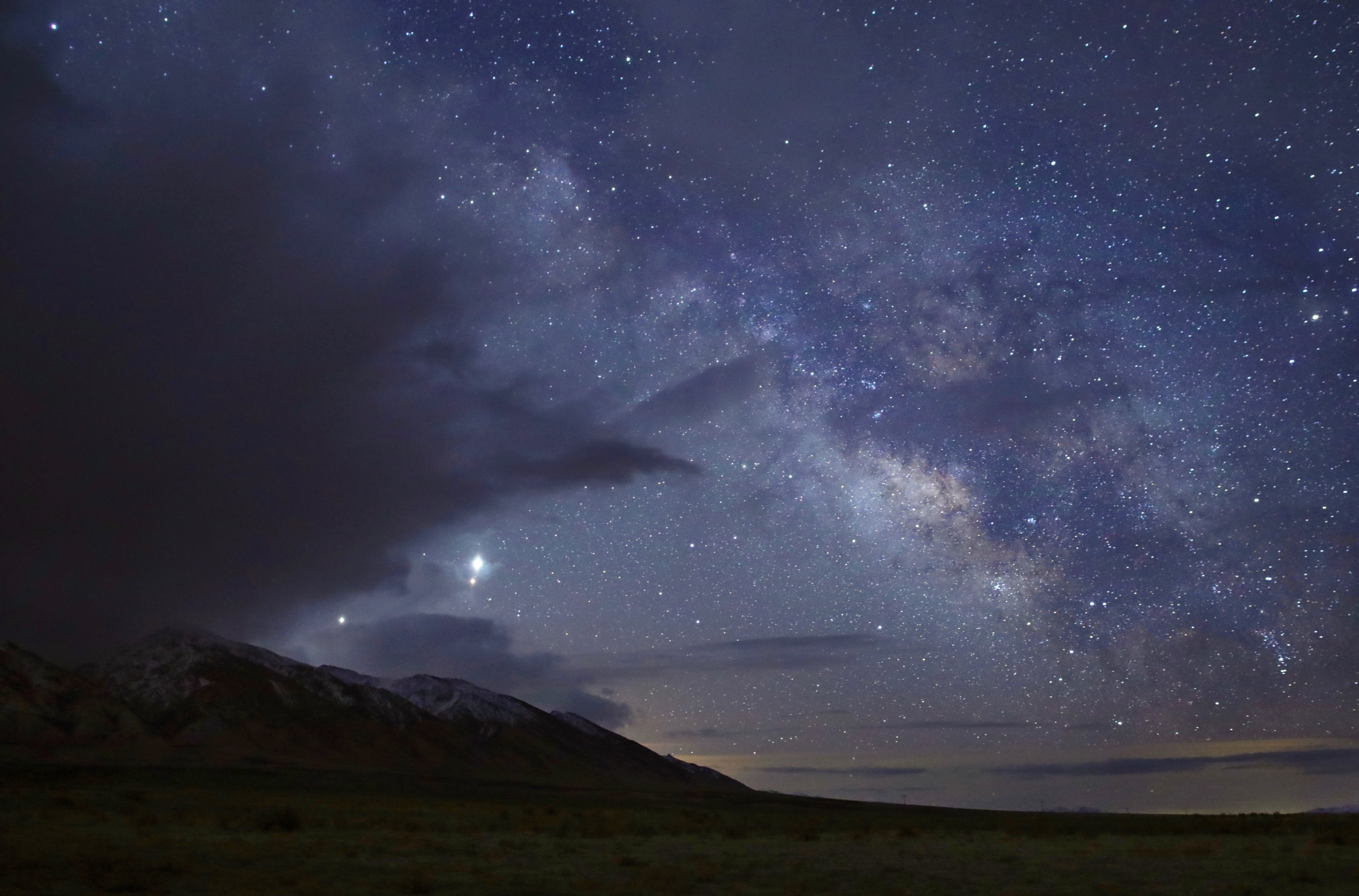milky way rising above a mountain with three planets visible as bright stars