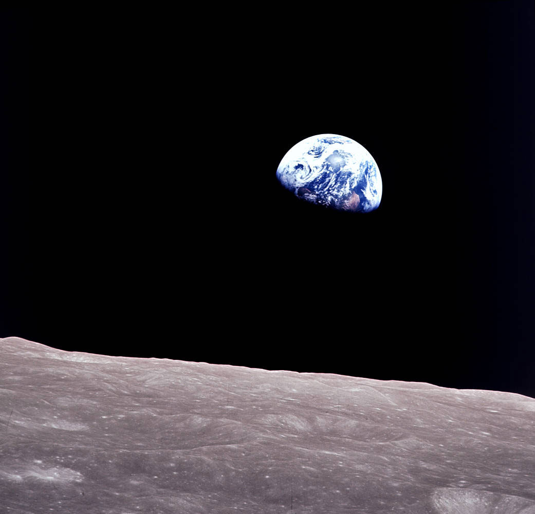 Earth rising above the cratered surface of the Moon.