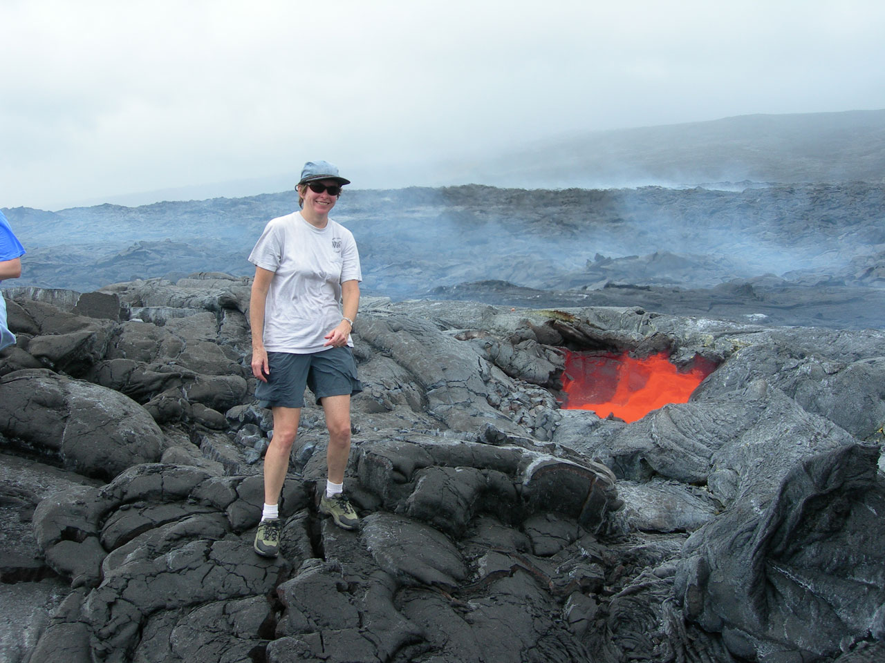 Woman standing next to active volcano vent glowing with hot lava.