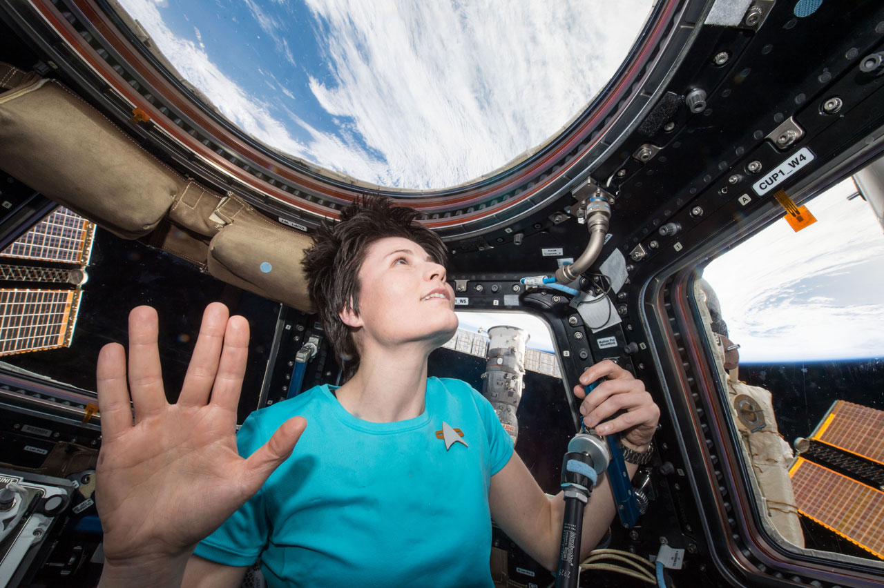 "Woman astronaut displays the Vulcan salute -- spreading four fingers into a big ""V"" -- while looking down onto the Earth from space."