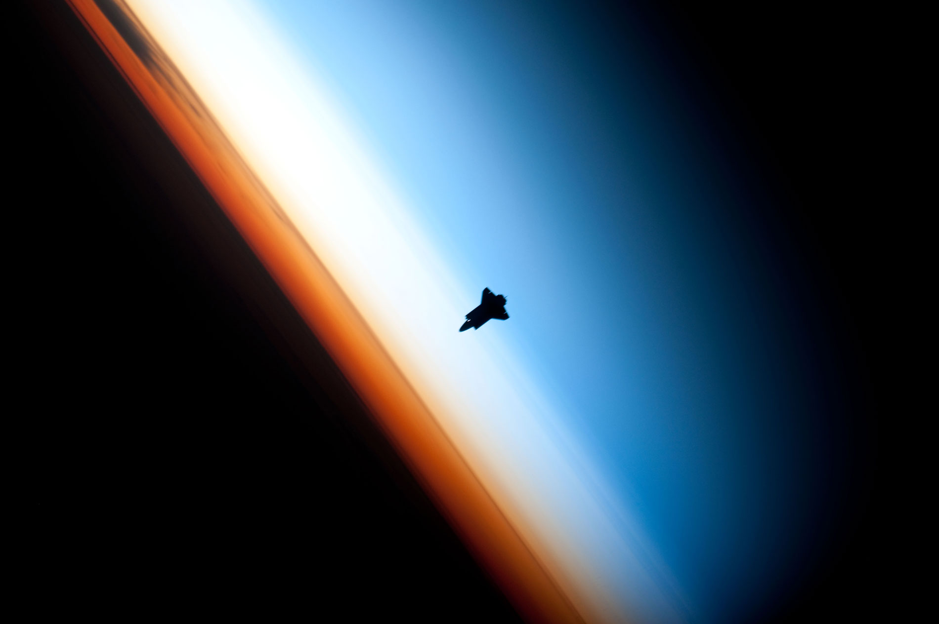 Image of Space Shuttle over a darkened Earth with three colorful layers of atmosphere visible.