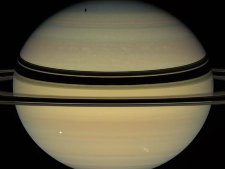 Saturn's rings cast dark bands across cloud tops in the northern hemisphere. Near the pole, an elongated shadow can be seen from Saturn's moon Tethys. Icy moons Dione (front right) and Enceladus (back right) are also seen by NASA's Cassini spacecraft.