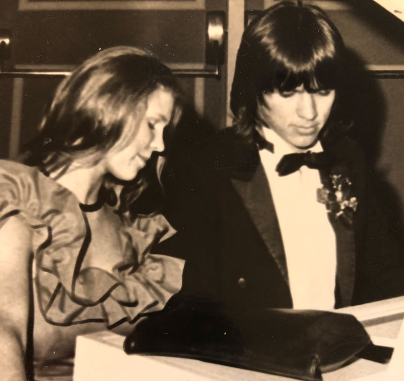 Lori Glaze and her future husband sitting together at a piano at their senior prom.