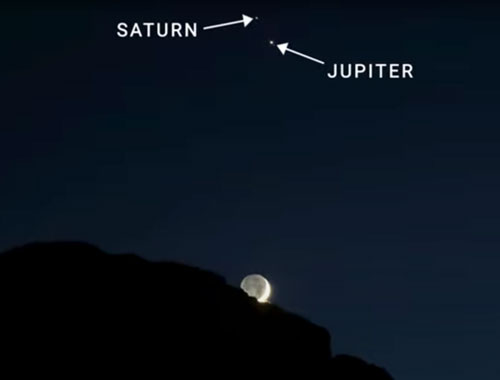 Jupiter and Saturn and the Moon behind a rocky peak.