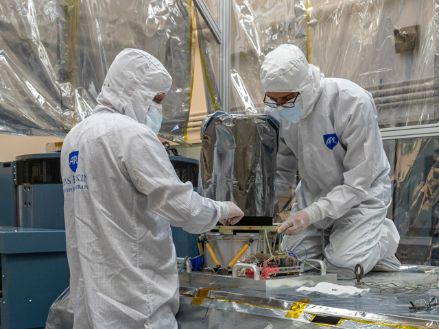 two people in protective gear work on an aluminum-covered instrument box