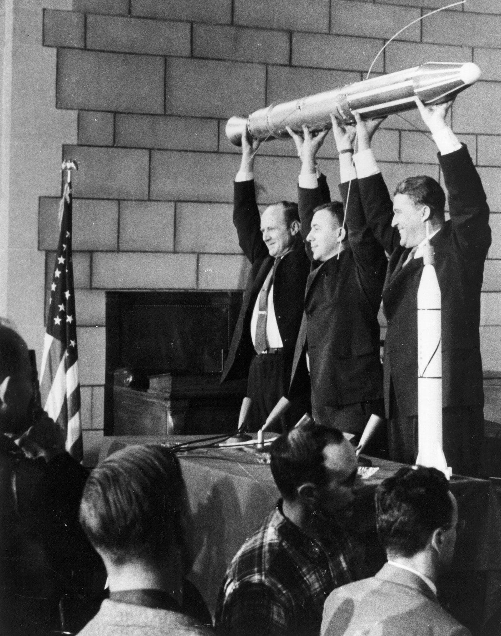Three smiling men holding up a spacecraft model.