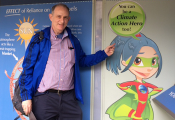Jack Kaye standing in front of a sign that reads, You can be a Climate Action Hero too!