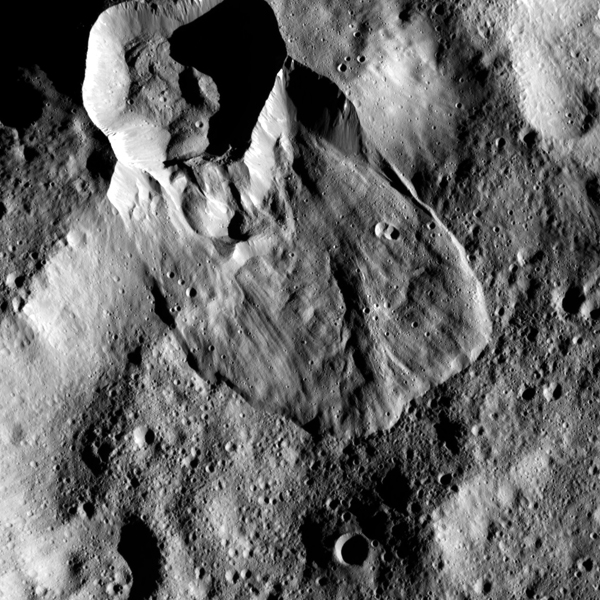 Orbiting Ceres, a section of the wall of the crater at the top of the picture collapsed, allowing material to flow downhill into the larger Ghanan Crater, only a portion of which is shown.