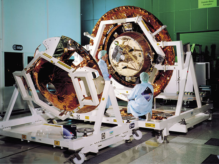 Color image of engineers working on spacecraft.