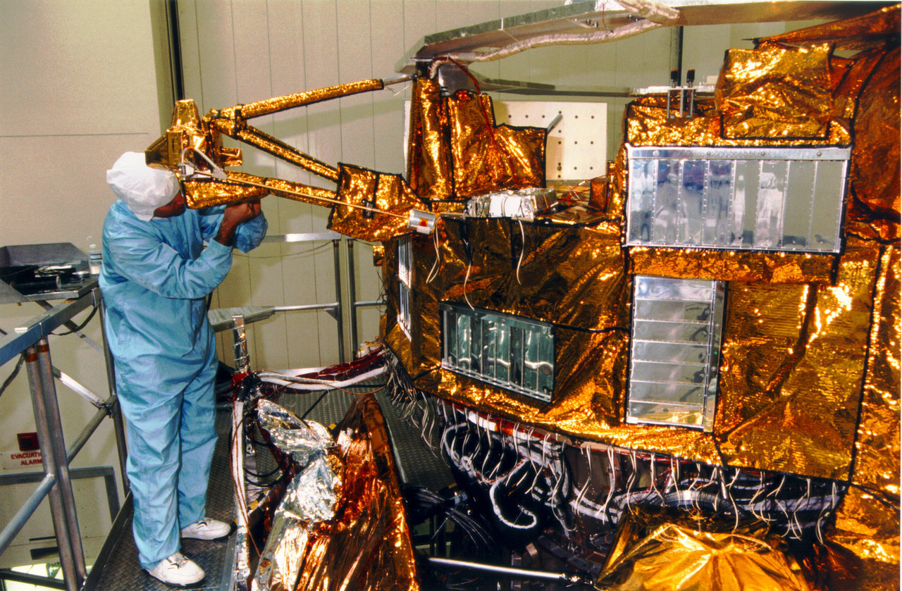 Color image of man working on spacecraft.