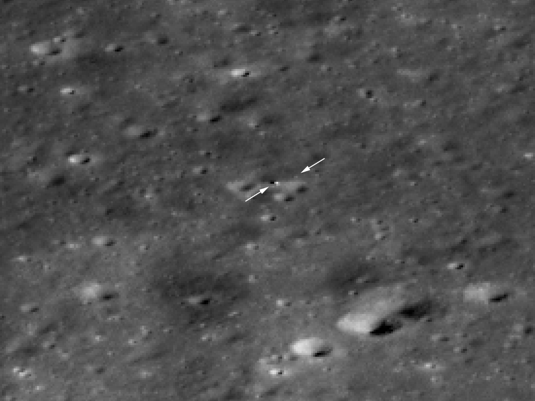 Rover and lander as small spots on the lunar surface.