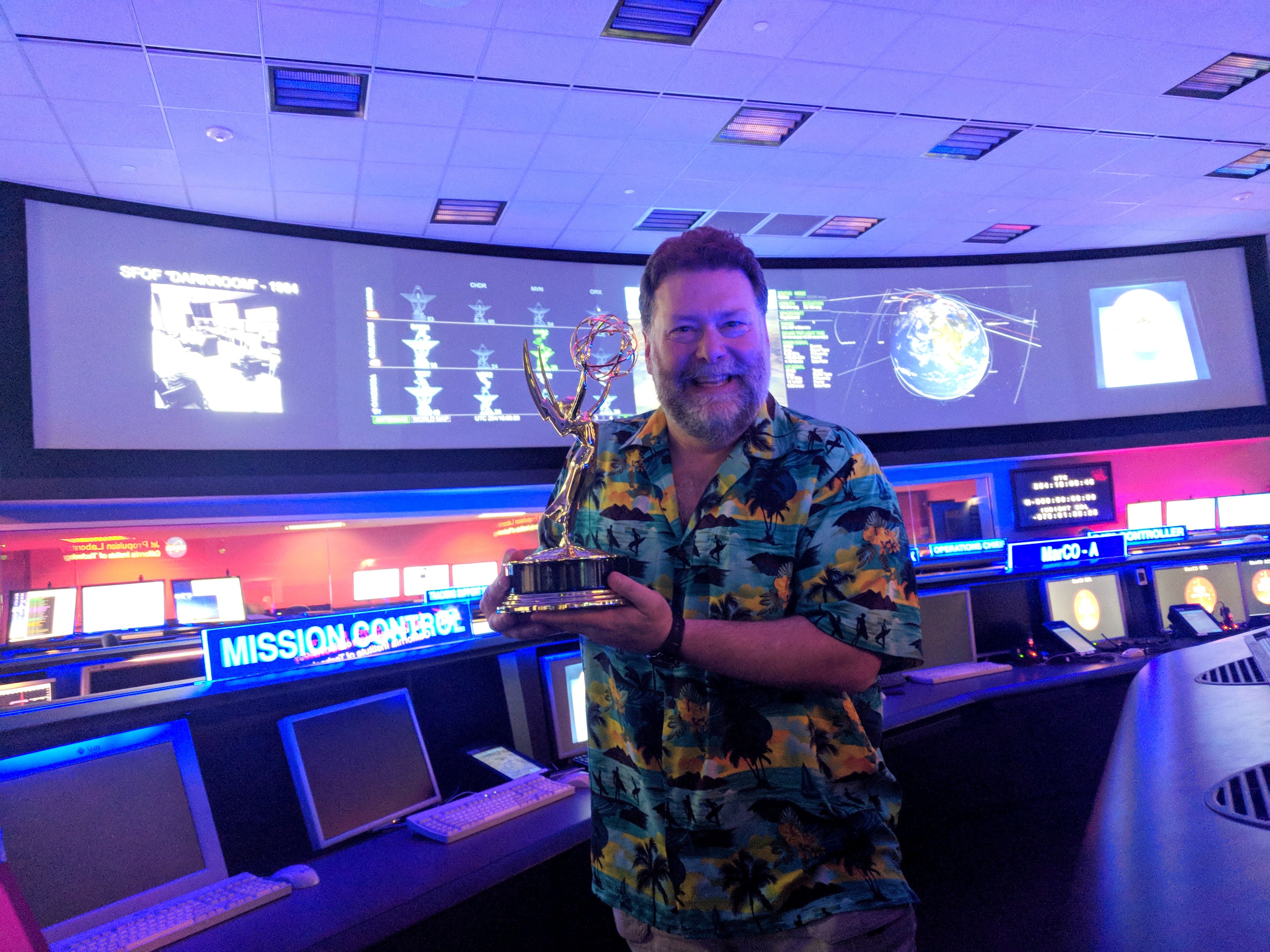 Todd in mission control holding an Emmy award statue.