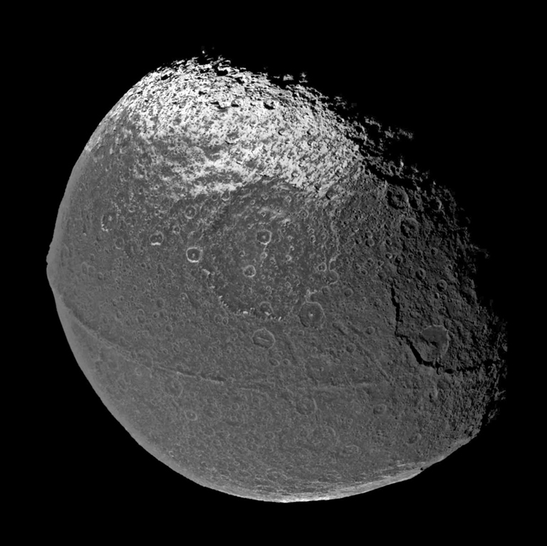Cassini flew past Iapetus on New Year's Eve 2004, capturing the four visible light images that were put together to form this global view. The scene is dominated by a dark, heavily-cratered region, called Cassini Regio, that covers nearly an entire hemisphere of Iapetus.