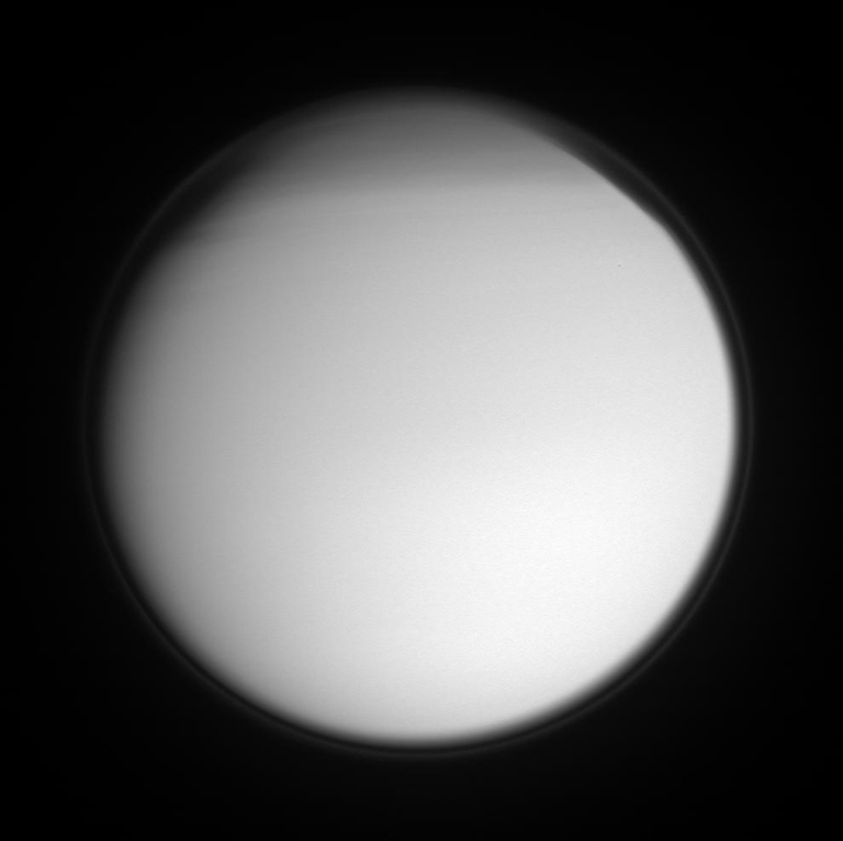 Titan's detached, high-altitude haze layer encircles its smoggy globe in this ultraviolet view, which also features the moon's north polar hood. The northern hemisphere is currently in its Winter season.
