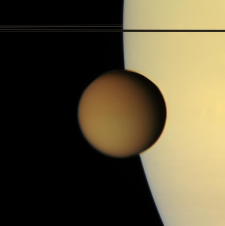 The murky orange disk of Saturn's moon Titan glides past -- a silent, floating sphere transiting Saturn. Titan's photochemical smog completely obscures the surface in such natural color views. Its high-altitude hazes are visible against the disk of Saturn as they attenuate the light reflected by the planet.