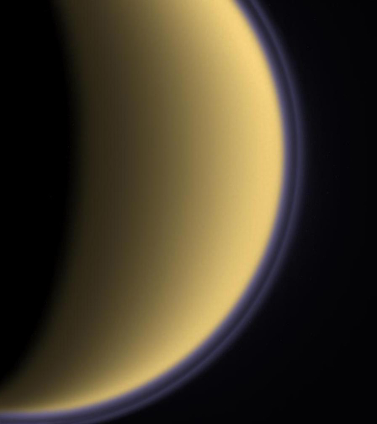 Encircled in purple stratospheric haze, Titan appears as a softly glowing sphere in this colorized image taken one day after Cassini's first flyby of the moon on July 2, 2004.