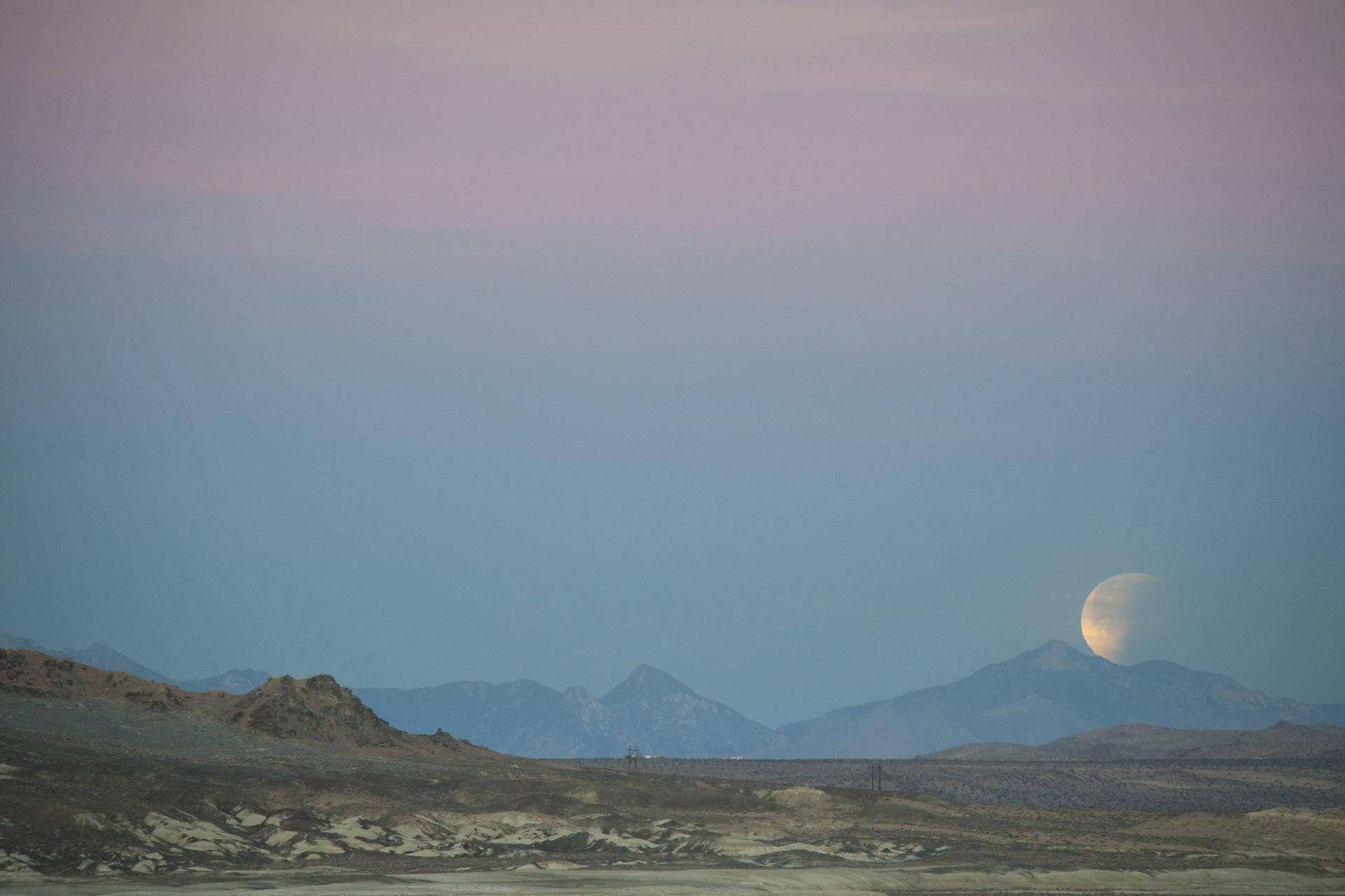 moon setting over desert landscape