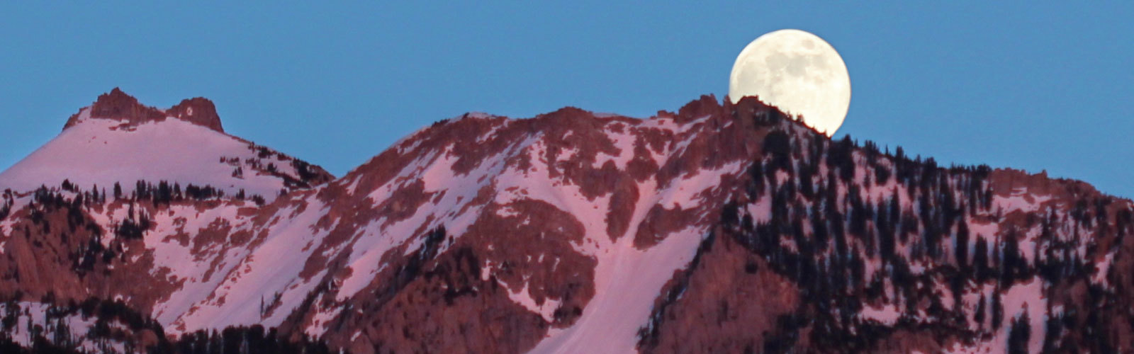Moon rising over snow-capped mountain peak.